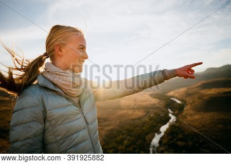 Caucasian Teen Pointing To Sunset Hiking Through Luscious Mountain During Golden Hour