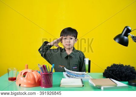 Boy Made A Gesture Like A Soldier, At The Homework Desk.