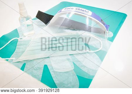 Corona Virus Prevention Kit Layed On White Table Background: . Green Mat; Green Face Mask; Disinfect
