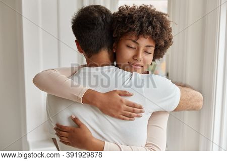 Back View Of Caucasian Guy Embraces Her Girlfriend, Stand Closely To Each Other, Express Love And Su