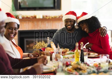 Couple wearing santa hat smiling and hugging each other while sitting and having lunch on dining table in the living room at home. christmas festivity tradition celebration concept