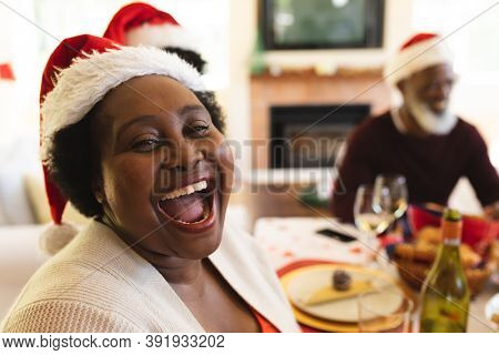 Portrait of senior woman wearing santa hat laughing while sitting and having lunch on dining table in the living room at home. christmas festivity tradition celebration concept