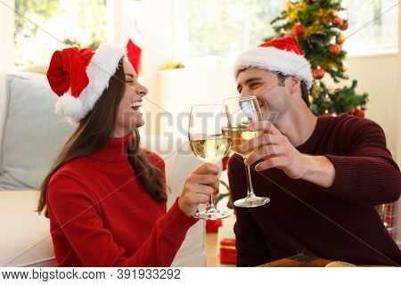 Couple wearing santa hat looking at each other smiling and toasting while sitting in the living room at home. christmas festivity tradition celebration concept