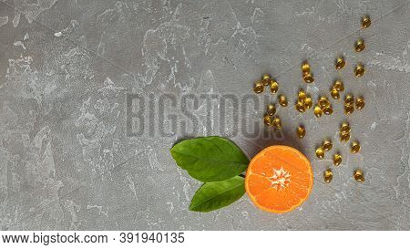 Cut Bright Tangerine With Leaves And Vitamins In Capsules On A Rough Gray Background Concept Of Heal