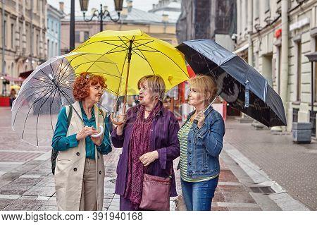 Senior Women With Umbrellas Talk On Street.