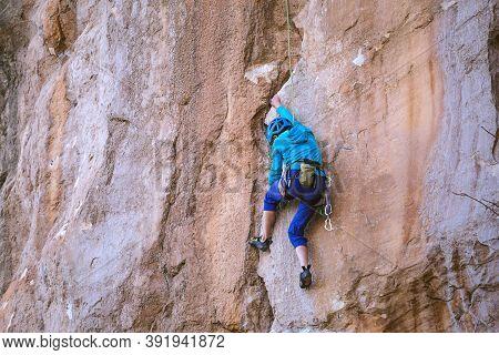 A Woman In A Helmet Climbs A Beautiful Orange Rock. Climbing Protective Equipment. Safety In Climbin
