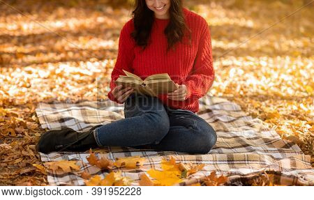Unrecognizable Millennial Woman In Casual Fall Clothes Sitting On Picnic Blanket And Reading Captiva