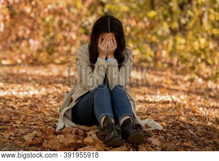 Unhappy Young Lady Sitting On Autumn Leaves At Park And Crying, Hiding Face In Her Palms. Desperate