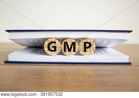 Concept Word 'gmp, Good Manufacturing Practice' On Wooden Circles Between Pages Of A Book On A Beaut