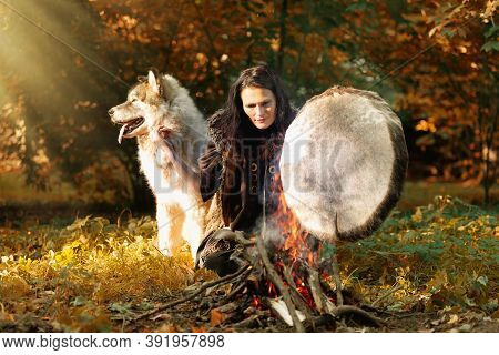 Shaman Woman Playing Her Shaman Sacred Drum In The Sunny Forest By The Fire, The Big Dog Alaskan Mal