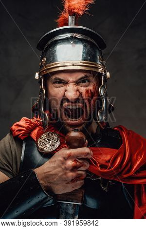 Savage And Armoured Roman Soldier With Red Cloak Screaming Staring At Camera Holding A Sword In Dark