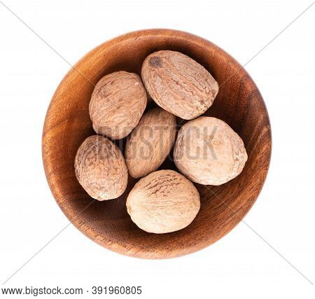 Nutmeg Isolated On White Background. Dry Whole Nutmeg In Wooden Bowl. Close-up. Top View.