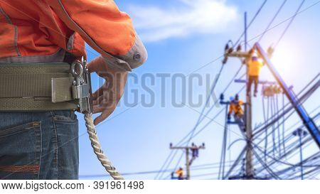 Midsection Of Electrician Lineman Wearing Safety Belt With Blurred Background Of Electrical Workers