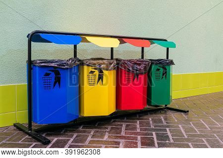 Row Of Four Colored Bins For Separate Garbage. Separate Collection Of Glass, Metal, Paper And Plasti
