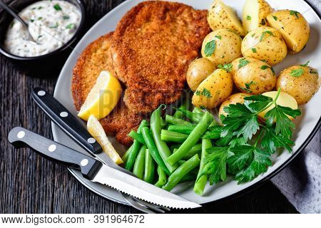 German Pork Schnitzel With Young Potatoes, Green Beans With Cutlery Served On A Plate With Lemon Wed