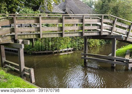 Wooden Decorative Footbridge Over A Canal In The Netherlands In The Background Of Plants And Buildin