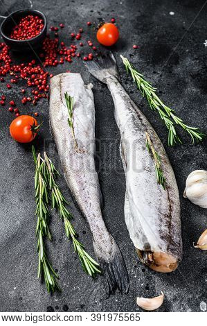 Raw Pollock Fish With Rosemary And Pink Pepper. Organic Seafood. Black Background. Top View