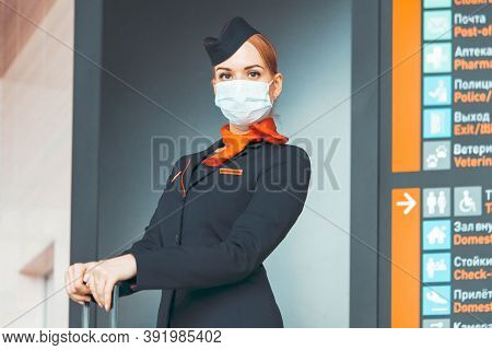 Close Up Of Beautiful Red Head Flight Attendant Wearing Protecting Mask And Stay Near Departure And