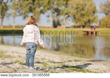 Back View Of Standing Blond Hair Little Girl On Lake Shore Outdoors.