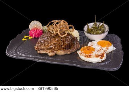 Amazing Gourmet Pork Steak On Blackstone, Isolated On A Black Background.amazing Gourmet Pork Steak