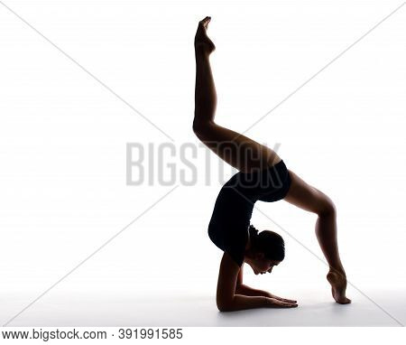 Professional Female Gymnast In Sportswear Performs A Handstand. Training, Elements Of Gymnastics, Ac