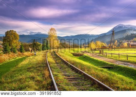 Railroad In Mountains With Snowy Peaks At Sunset In Autumn. Industrial Landscape With Railway Statio