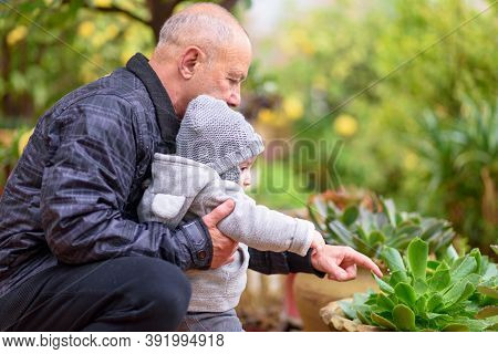Two Generations, Family Love. Happy Grandfather With Grandson Outdoor Together. Grandparent Shows Hi