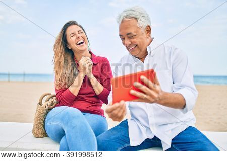 Middle age hispanic couple using touchpad sitting on the bench at the beach.