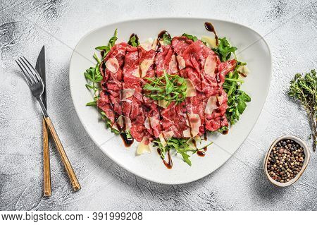 Beef Carpaccio On White Plate With Parmesan Cheese And Arugula. Gray Background. Top View.