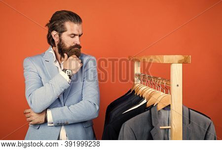 What To Choose. Handsome Man In Smart Casual Wear Looking At Suits And Choosing. Stylish Mens Clothi