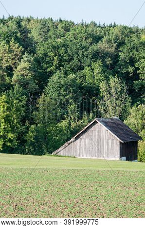 Hilly Landscape With Field And Mixed Forest With A Wooden Barn