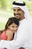 Man and young girl outdoors in park embracing and smiling (selective focus) poster