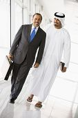Two businessmen walking in corridor smiling (high key/selective focus) poster