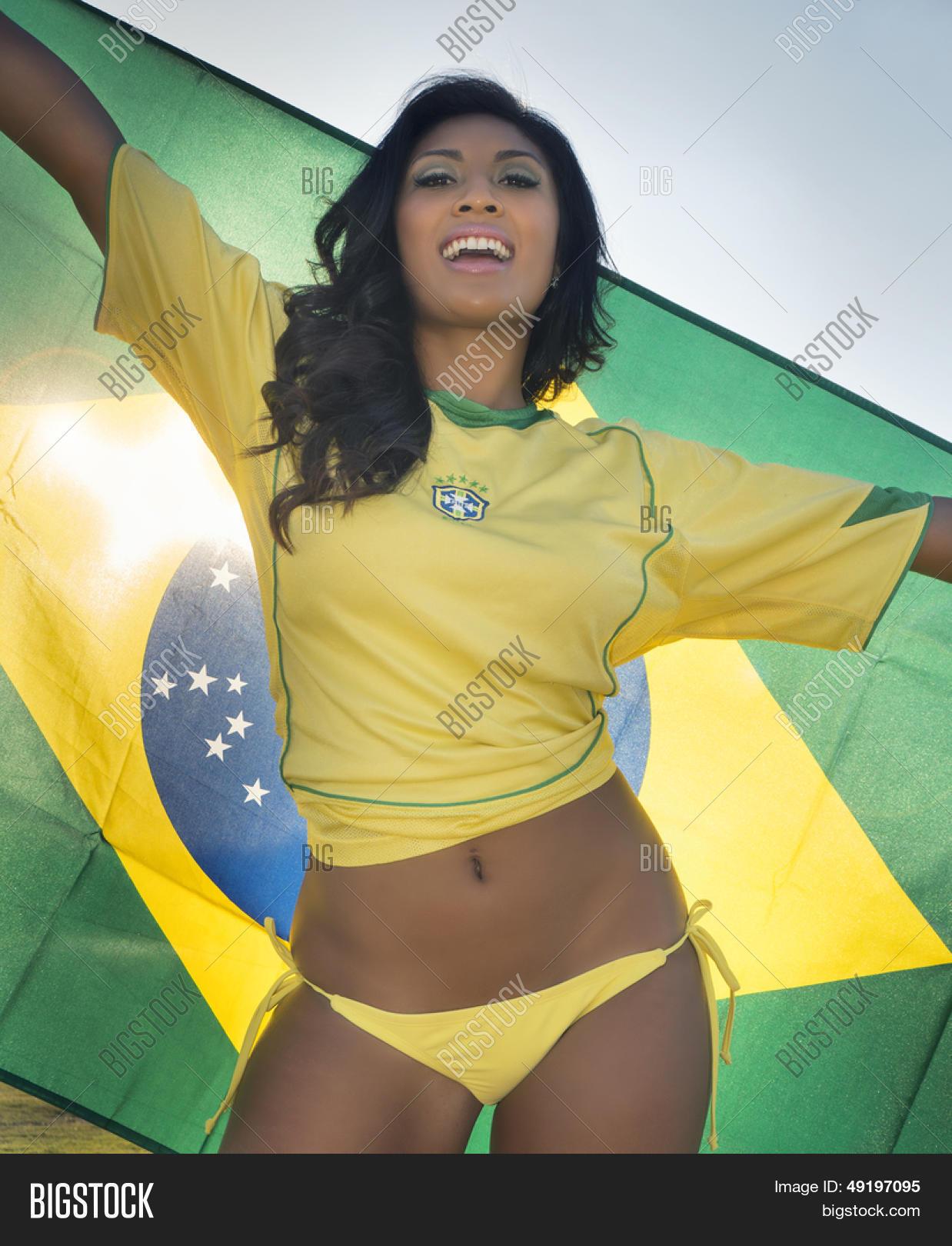 1ec1dcc7737 Beautiful happy smiling young woman holding Brazil flag wearing soccer top  and bikini bottom