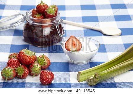 A basket of strawberries a ready bottling jar of strawberry jam a wooden spoon sucre pieplant and a half of a strawberry laying on a checkered tablecloth. poster