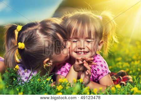Happy Girls Twin Sisters Kissing And Laughing In The Summer Outdoors
