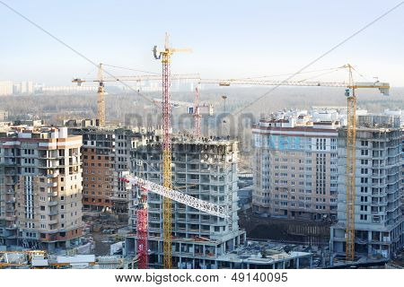 Many residential multi-storey buildings under construction and yellow cranes at sunny day.