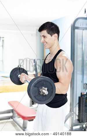Smiling handsome man lifting heavy free weights at the gym