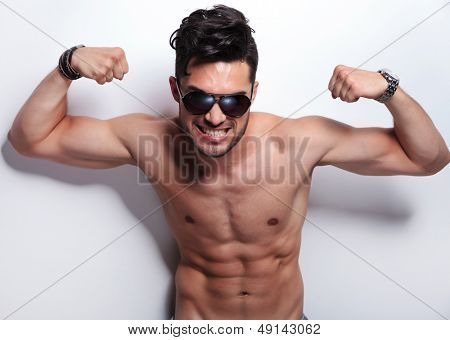 closeup of a fierce young topless man showing his biceps while looking at the camera. on light gray background