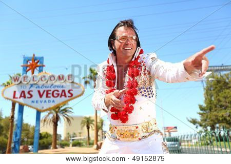 Elvis look-alike impersonator man and Las Vegas sign on the strip. People having fun and Viva Las Vegas concept image with Elvis impersonator dancing doing some crazy moves outdoor.