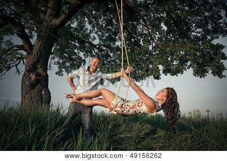 Beautiful girl on the swing in the forest with her boyfriend