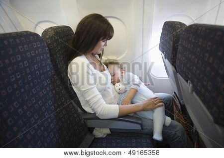 Baby girl sleeping on mother's laps while traveling in airplane