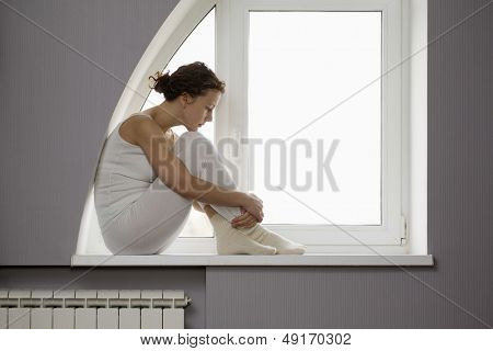 Profile shot of sad woman sitting on window sill