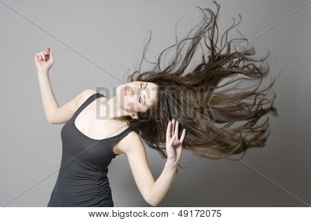 Young woman with long brown wavy hair dancing against gray background