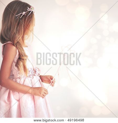 Beautiful little girl wearing fairy costume with magic wand