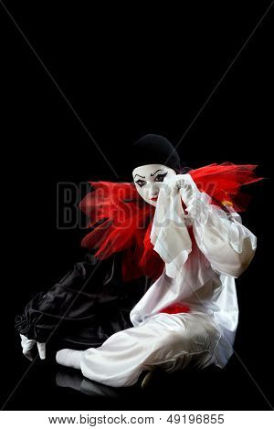 Unhappy Pierrot crying in a white handkerchief