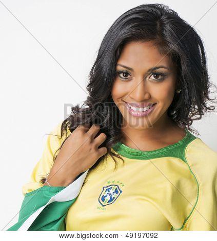 Beautiful Brazilian young woman with happy smiling woman wearing Brazil football top
