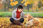 Young woman in a park stroking her retriever dog poster