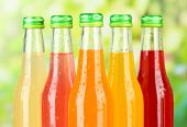 Bottles with tasty drinks on bright background