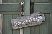 Gone to Texas sign on old green door. poster